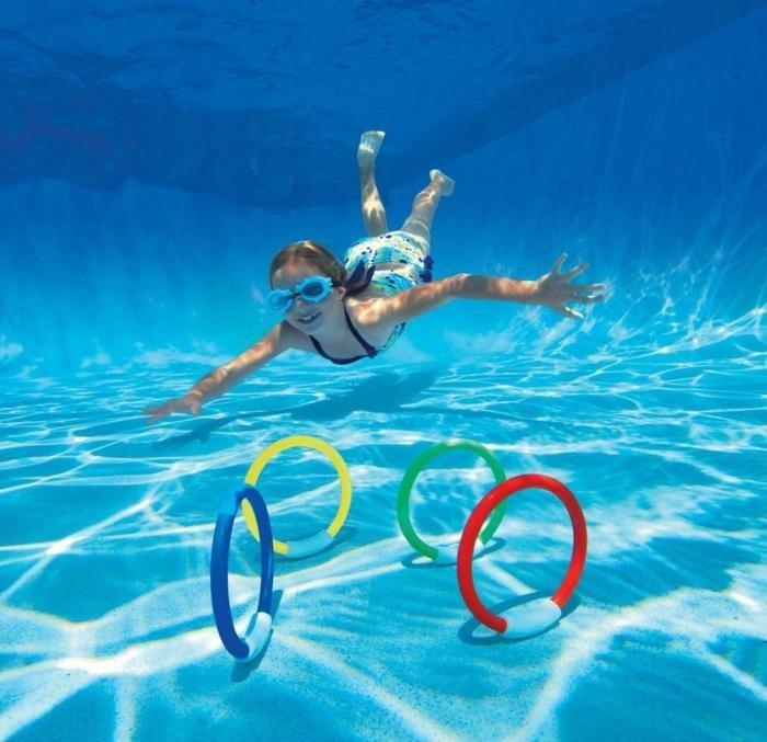 Girl diving for rings in swimming pool