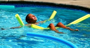 Child in water laying on back relaxing on noodles